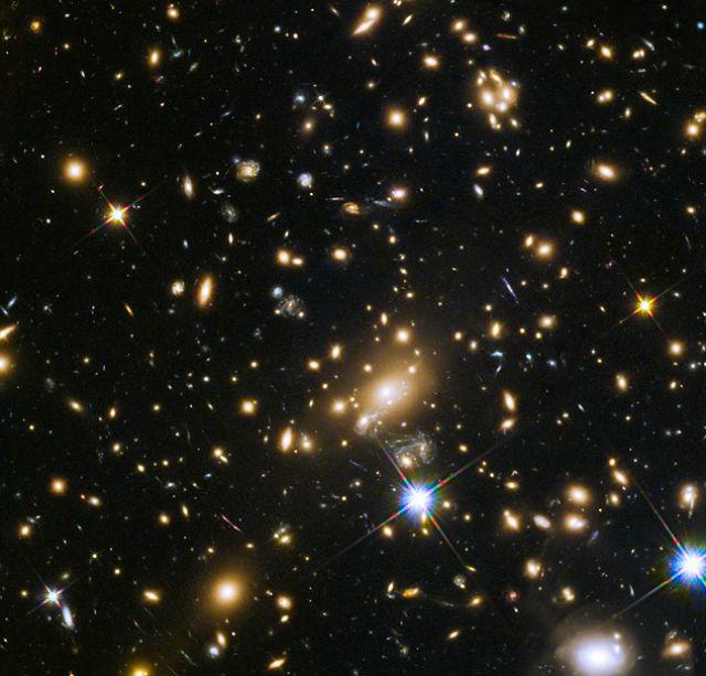 На пути к Земле свет от сверхновой искривляется гравитационной линзой — галактикой (фото NASA/ESA/GLASS team).